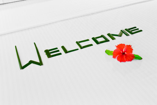 Word Welcome and flower on bed in hotel