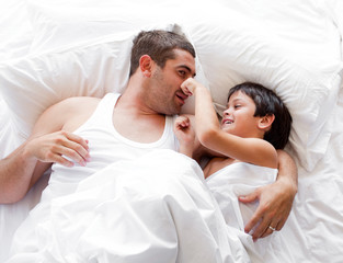 Father and son having fun together on bed