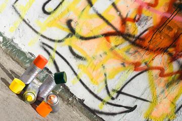 Aerosol paint near graffiti painted wall
