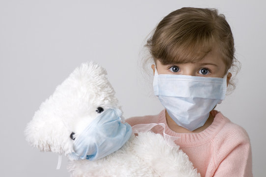 Little girl with teddy bear  wearing  a protective  mask