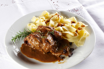 Rabbit steak with pasta noodles , rosemary and spicy sauce