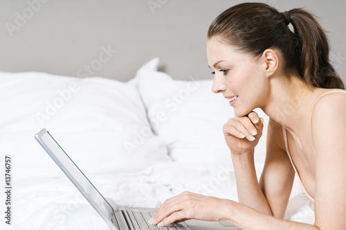sch ne frau surft im internet im bett stockfotos und lizenzfreie bilder auf bild. Black Bedroom Furniture Sets. Home Design Ideas