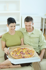 Happy couple eating pizza