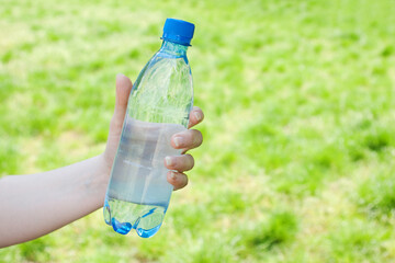 Hand offering bottle of water against green blurred background