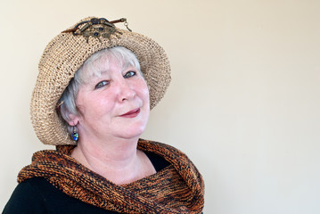 Mature lady wearing hat, blue earrings and knitted garment
