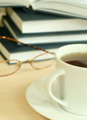 Cup of tea, books and eyeglasses
