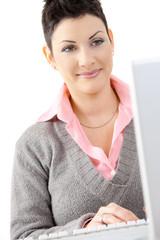 Happy businesswoman using computer