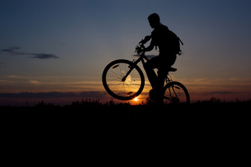 boy on a bicycle in the sunset