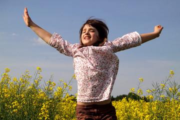 Mädchen springt in einem Rapsfeld hoch
