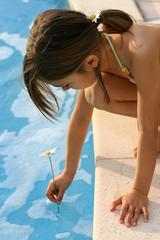jouer avec une pâquerette au bord de la piscine