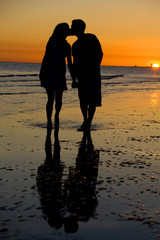 A couple kissing at sunset on the beach