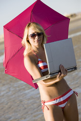 A woman on her computer at the beach