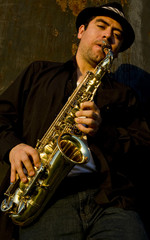 saxophonist plays outdoors against an industrail
