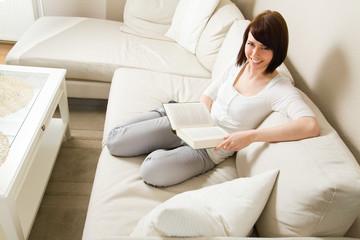 Mit Buch auf dem Sofa