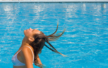 Girl splashing water with her long hair in a pool