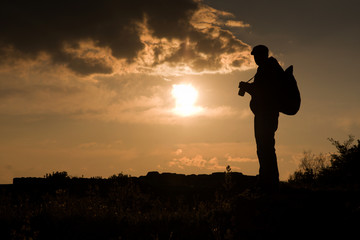 Photographer silhouette at sunset in mountains