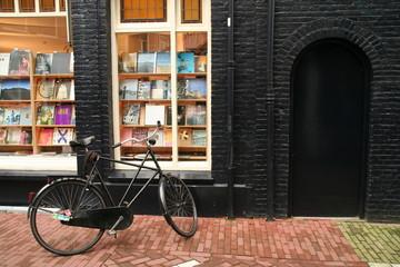 Bicycle behind a book shop and black brick wall.