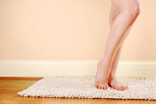 A woman's naked legs standing on a bath mat