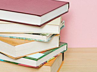 Pile of colorful books isolated on pink background