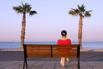 Lonely girl sits on a bench near sea beach