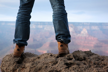 Male feet in hiking boots standing on edge of a cliff
