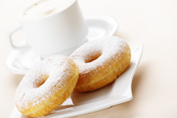 Two donuts with cup of coffee