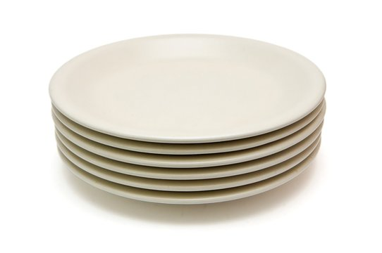 Stack of plain beige dinner plates isolated
