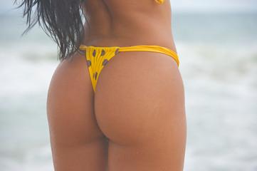 Bikini girl with polka dot g-string butt on the beach