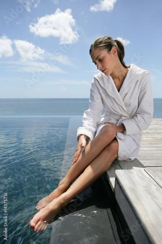 Jolie femme en peignoir assise au bord d 39 une piscine for Peignoir piscine