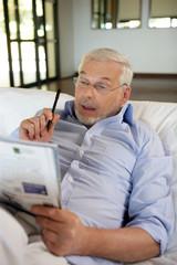 Homme senior assis dans un canapé faisant des mots-croisés