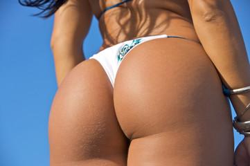 tanned Bikini Girl g-string butt against blue skies