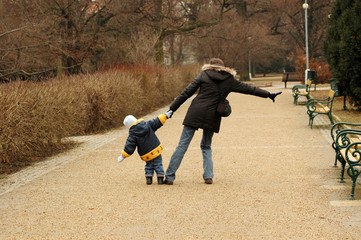 Woman and child walking in the park.