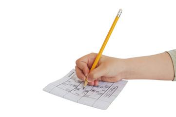 child hand writing on sudoku game isolated on white