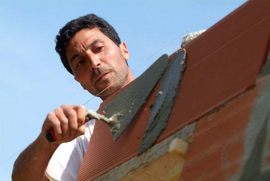 maçon posant des briques dans un chantier