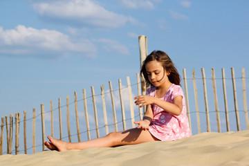 fillette faisant couler du sable dans ses mains 2