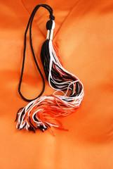 Graduation tassel in black, orange and white lying on orange silk