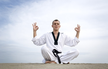 Martial art master  meditate, sitting at sand over sky