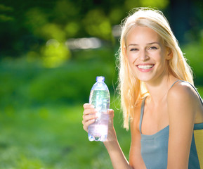 Young woman with bottle of water outdoors