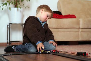 KLeiner Junge beim spielen mit Autorennbahn