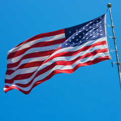 An American flag blows in the wind in front of a blue sky