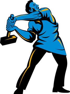 Worker slinging a sledge hammer