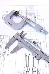 Micrometer and caliper on blueprint vertical. Shallow dof