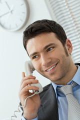 Young businessman talking on landline phone at office,