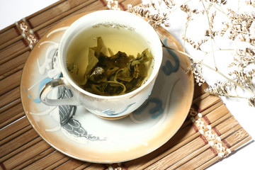 Green tea in a chinese cup with a tea leafs