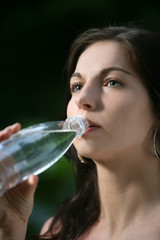 Beautiful young woman in the park. Drinks water.
