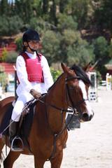 niña a caballo en concurso hípico esperando entrega premio