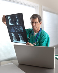 Doctor at His Laptop Reviewing Patient Radiology Scans