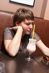 Sad woman drinks milk shake in a cafe