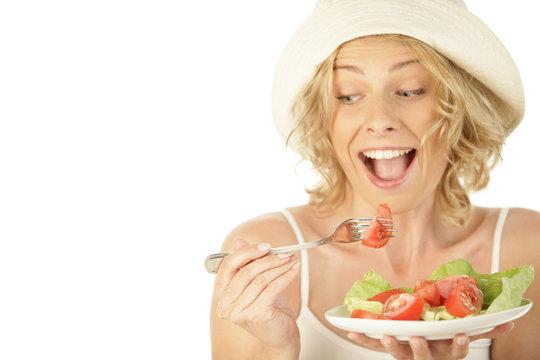Blonde woman eating vegetable salad