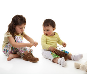 Elder sister trains younger sister to fasten laces